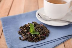 Dry green tea leaves and cup of aromatic beverage on table stock photos