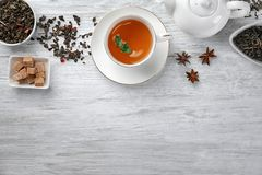 Dry green tea leaves and cup of aromatic beverage on table royalty free stock images