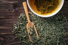 Dry green tea leaves and cup of aromatic beverage on table royalty free stock photos