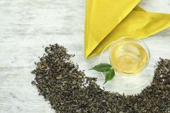 Dry green tea leaves and cup of aromatic beverage on wooden background royalty free stock photos