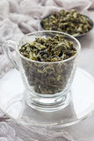 Dry green tea leaves in cup and on background, vertical Royalty Free Stock Image