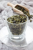 Dry green tea leaves in cup and on background, vertical Royalty Free Stock Images