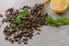 Dry green tea leaves and lemon on table stock images
