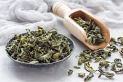 Dry green tea leaves on metal plate and on background,horizontal Royalty Free Stock Photography