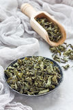 Dry green tea leaves on metal plate and on background Stock Photo