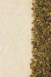 Dry green tea leaves on a sackcloth. Background royalty free stock photo