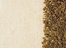 Dry green tea leaves on a sackcloth. Horizontal background Stock Photo