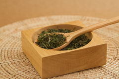 Dry green tea leaves in wooden spoon Stock Image