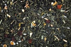 Dry green tea with petals of flower and fruit Stock Images