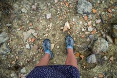 Legs of woman traveller standing on a ground of Cyprus island full of broken ancient pottery shards stock images