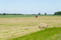 Dry haystack roll and blur tractor ted hay field Royalty Free Stock Image