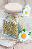 Dry herbal chamomile tea in a jar with fresh chamomile flowers on background Stock Photo