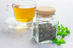 Dry herbal mint tea in a jar with cup of tea on background Stock Photos