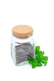Dry herbal mint tea in a jar with fresh peppermint on background, isolated on white Royalty Free Stock Photography