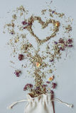 Dry herbal tea placed in the shape of heart on the gray background.  Stock Photo