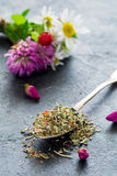 Dry herbal tea in teaspoon. On slate background. Closeup view Stock Images