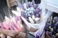 Dry herbs colorful purple and pink bouquets at flower shop. Beautiful bundles of pink and blue dried spikelets at a market - tinted lavender, canary grass, bunny stock photos