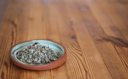 Dry Hyssop on a plate. Of clay, wooden table royalty free stock photography