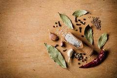 Dry ingredients for cooking on wooden table. Sea salt, garlic, bay leaf, pepper and clove Stock Photography