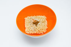 Dry instant Noodle in orange bowl on the white background Royalty Free Stock Photos
