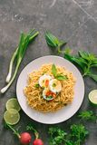 Dry instant noodles put egg with fresh herbs, garnish of cilantro and Asian basil, lemon, lime on dark stone background.  stock photo
