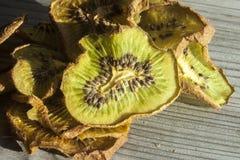 Dry kiwi. A pile of dry, green kiwi. On wooden background Royalty Free Stock Photos