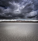 Dry lake bed. With storm clouds Stock Images