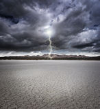 Dry lake bed. With storm clouds and lightning Royalty Free Stock Photo