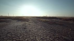 Dry land with distant windmills at the horizon. Desolate landscape with dry land and silhouettes of distant windmills at the horizon at sunset in summer stock video footage