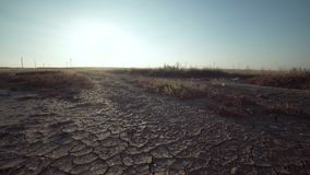 Dry land with distant windmills at the horizon. Desolate landscape with dry land and silhouettes of distant windmills at the horizon at sunset in summer stock footage