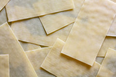 Dry lasagna pasta sheets on black textured wood from above. Abst Royalty Free Stock Images