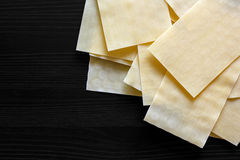 Dry lasagna pasta sheets on black textured wood from above. Spac Royalty Free Stock Photos