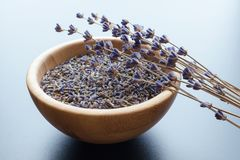 Dry lavender flowers. Wooden bowl with dried lavender tea and flowers over blue background stock photos