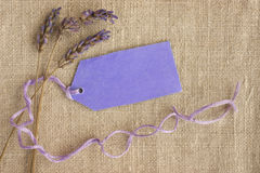 Dry lavender, gift tag label, purple. Dry lavender tied with a string and attached to a purple gift tag. Concept for memories, occasions, labels. On linen royalty free stock photos