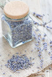 Dry lavender tea in glass jag and on wooden background, vertical. Dry lavender tea in glass jag and on wooden background royalty free stock photos