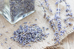 Dry lavender tea in jag and on wooden background, horizontal. Dry lavender tea in glass jag and on wooden background, horizontal stock image