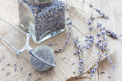 Dry lavender tea in tea infuser spoon and glass jag on wooden background. Horizontal stock photos