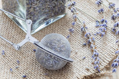 Dry lavender tea in tea infuser spoon and glass jag on wooden background, horizontal. Closeup stock photo