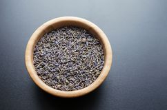 Dry lavender tea. Wooden bowl with dried lavender tea over grey background stock photos