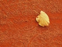 Dry leaf an tennis court. Dry light red crushed bricks surface on outdoor tennis ground. End of season. Stock Photos