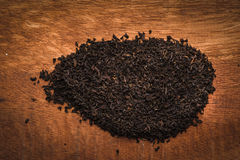 Dry leaves of black tea on the redwood table Stock Photos