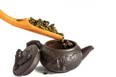 Dry leaves of tea tieguanyin, scattered around a porcelain teapot, a tea blade. stock photo