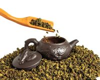 Dry leaves of tea tieguanyin, scattered around a porcelain teapot, a tea blade. stock photos