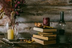 Dry leaves in a vase. vintage interior. books, candle and oli la. Mp on the table. wooden background.autumn royalty free stock photo