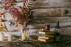 Dry leaves in a vase. vintage interior. books, candle and oli la. Mp on the table. wooden background.autumn royalty free stock images