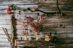 Dry leaves in a vase. vintage interior. books, candle and oli la. Mp on the table. wooden background.autumn royalty free stock photography