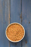 Dry lentil on bowl on blue backround Stock Photo