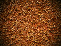 Dry light red crushed bricks surface on outdoor tennis ground. Detail of texture Royalty Free Stock Image