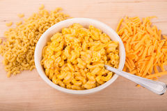 Dry Macaroni and Grated Cheese with Bowl of Mac n Cheese. A bowl of macaroni and cheese with cayenne or paprika pepper Royalty Free Stock Image
