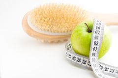 Dry massage brush with tape measure and single green apple on white desk. Health and diet. Dry massage brush with tape measure and single green apple on white stock photos